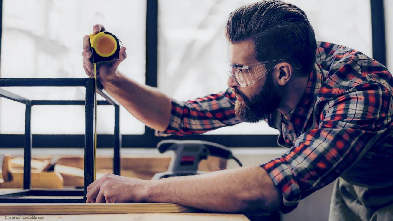 Ein DIY Handwerker misst ein Vierkantrohr